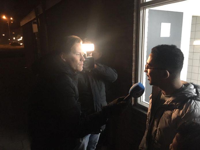 Een jongere uit de buurt staat de pers te woord.