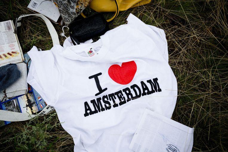 Een t-shirt met de tekst 'I love Amsterdam' tussen bagage van slachtoffers tussen de wrakstukken. Beeld null