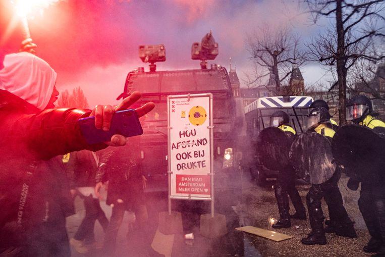 Betogers tegenover politie op het Museumplein in Amsterdam. Beeld Joris van Gennip
