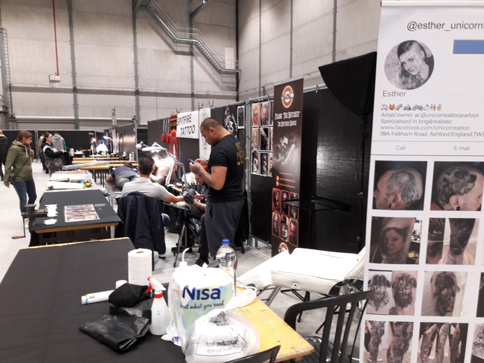 In sommige shops op de Tattoo-beurs op Breepark in Breda werken artiesten al aan tattoos. Foto Berry van der Heijden.