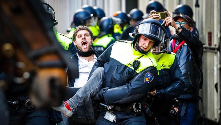 De bezetters worden door de politie een voor een uit het gebouw gehaald. Beeld ANP