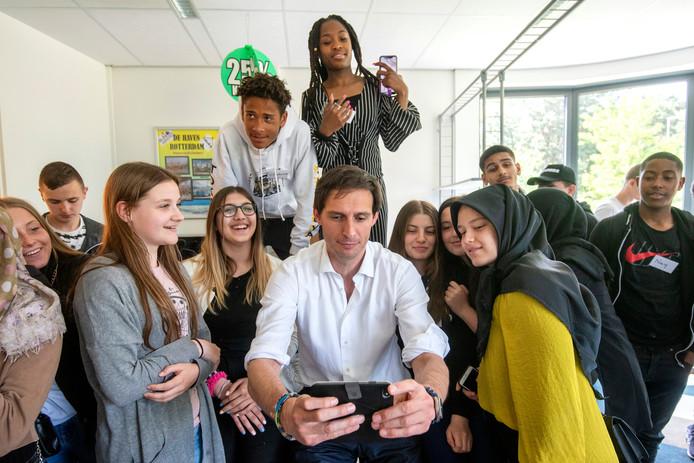 Wopke Hoekstra bereidt zich op voor op het maken van een selfie met de groep na de gastles over leren omgaan met geld aan leerlingen op Vmbo 't Venster in Arnhem.
