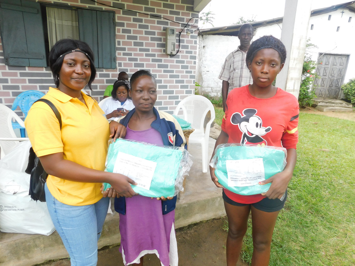 Inwoners van de regio Bomono tonen muskietennetten die ze van de Casey Troy Foundation hebben gekregen.