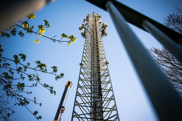 Monteurs aan het werk bij een zendmast voor mobiele netwerken die door een brand zwaar beschadigd is geraakt.  Beeld ANP