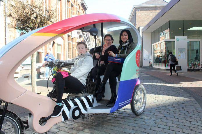 De eerste toeristen nemen plaats in een fietstaxi.