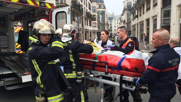 Brandweermannen laden een gewonde in de ambulance Beeld ANP