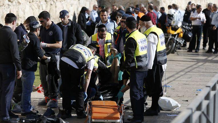 Het lichaam van een van de Palestijnen wordt weggehaald. Beeld AFP