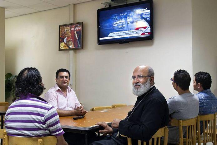 In de Koptische kerk aan de Eindhovense Stokroosstraat staat de televisie permanent op de Egyptische nationale omroep. Tweede van links: Esam Ebid. In het midden: abuna ('vader') Youssef Rizkalla. Foto René Manders
