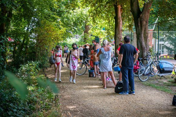 Mensen staan aan te schuiven aan zwemvijver Boekenberg