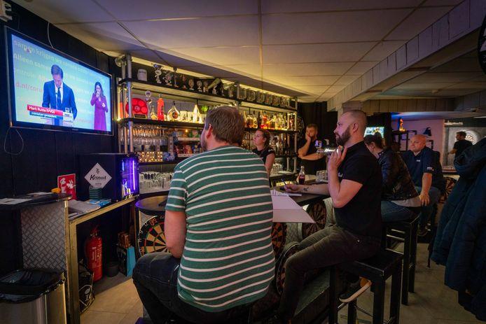 Eigenaar Joshua van Rootseler van dartcafé Dubbel 10 kijkt naar de persconferentie.