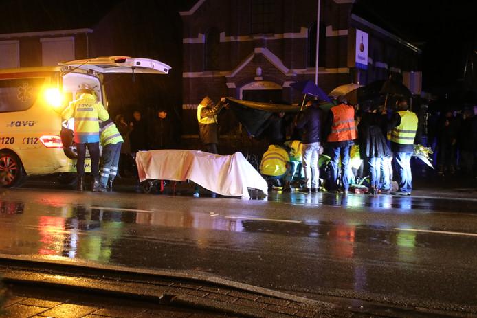 Omstanders proberen met zeil en paraplu's de hulpverleners droog te houden terwijl ze de fietser helpen die in Renswoude door een onbekende automobilist werd geschept.
