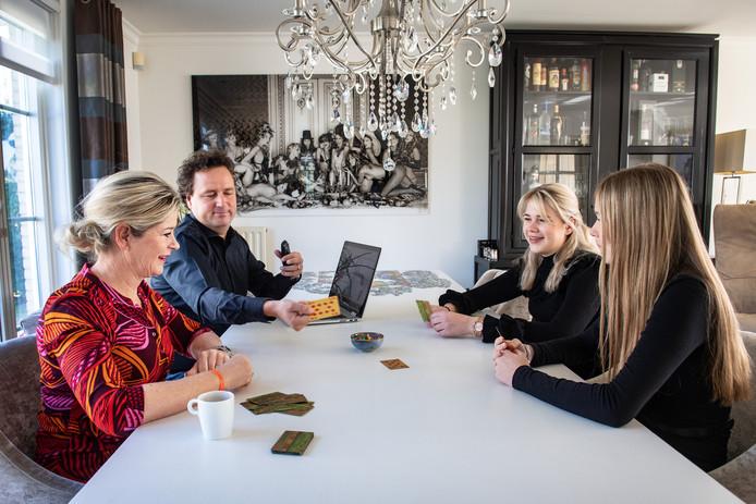 Stan van den Dobbelsteen speelt het oude kaartspel toepen met zijn vrouw en dochters. Maar het werk gaat door dus ook de laptop staat op tafel.
