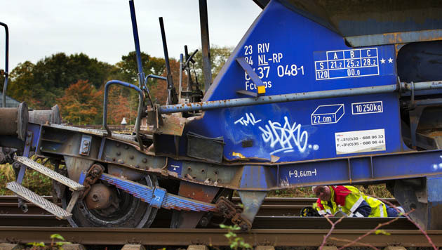 Onderzoekers van Prorail nemen de schade op aan een ontspoorde goederenwagon. Een met ballast beladen wagon ontspoorde en vernielde 4 kilometer spoor tussen Borne en Almelo.
