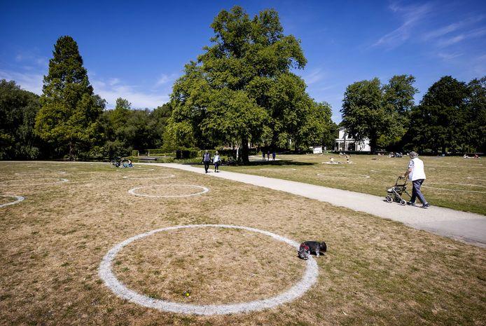 Cirkels die door de gemeente in de ligweides van Het Park in Rotterdam zijn aangebracht. Bezoekers worden gevraagd plaats te nemen in de cirkels. De gemeente hoopt op deze manier de 1,5 meter afstand te kunnen waarborgen.