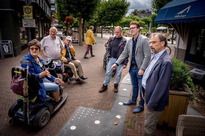 Dave Herms (tweede van rechts) met wijkbeheerder Karst-Jan Keuvelaar (derde van rechts) en enkele mensen van de Cliëntenraad Integraal Gehandicaptenbeleid Wijchen bij de geleidelijn met ijzeren noppen. Geheel links Odette Delhij.