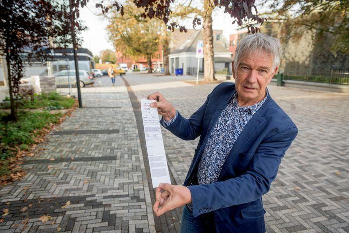 Herbert Simmelink met zijn parkeerbon toen de zwarte betegeling op het wegdek langs de Van Galenstraat nog de indruk wekte van parkeervakken.