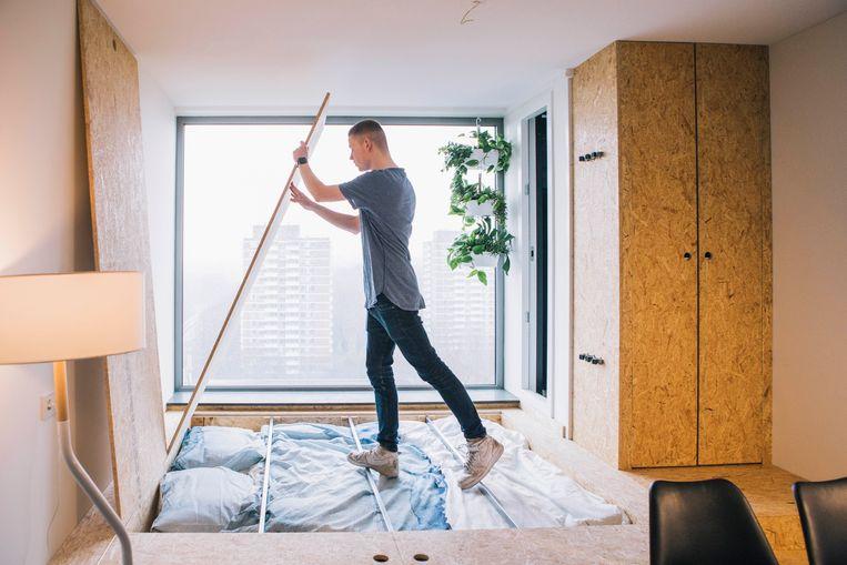 Pim Anneveldt (23) woont in een micro-appartement in Amsterdam. Amper 30 vierkante meter groot is zijn woonst.  Beeld Marcel Wogram