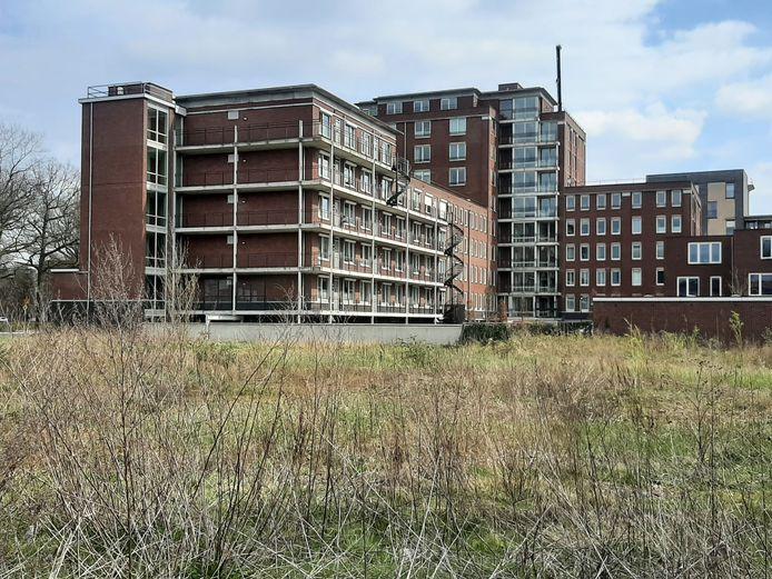 Het braakliggende terrein aan de Costerweg waar studentenkamers komen. Op de achtergrond appartementencomplex Costerstaete.