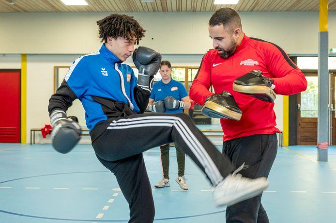 Jercy (15, links) is op school aan het kickboksen met jongerenwerker Yassin Lees. Op de achtergrond Johnny Toonen, uit dezelfde klas.