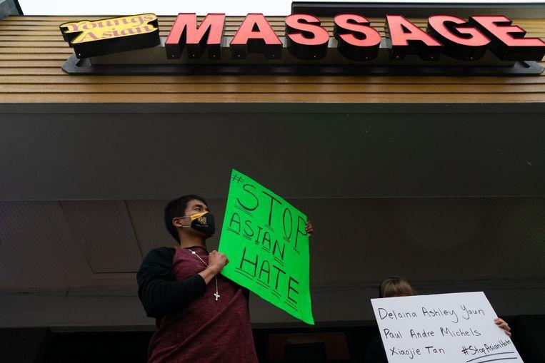 Een man houdt een boord omhoog met de tekst 'stop haat jegens Aziaten' bij een van de aangevallen massagesalons. Beeld AFP