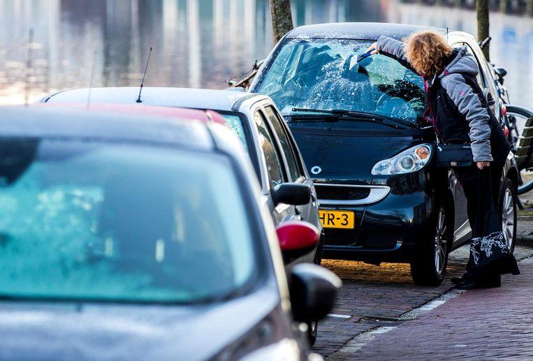 Een vrouw krabt de ruit van een auto schoon. De temperatuur was op veel plaatsen rond het vriespunt.  Beeld anp