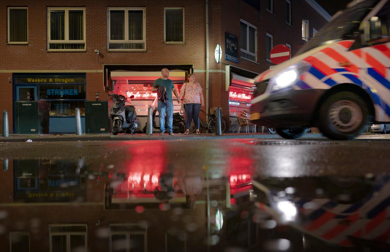 Een politiebusje passeert café De Wereld in de Schilderswijk waar vorige week avonden lang rellen plaatsvonden.  Beeld