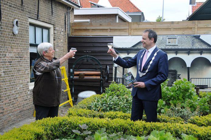 Ria Geluk en burgemeester Jack van der Hoek proosten op de lancering van de wandelgids in de tuin van Brusea, met links 't Vissersuusje en op de achtergrond een foto van de beurs waar vroeger mossels werden verhandeld en  die ook nog in het echt is te zien