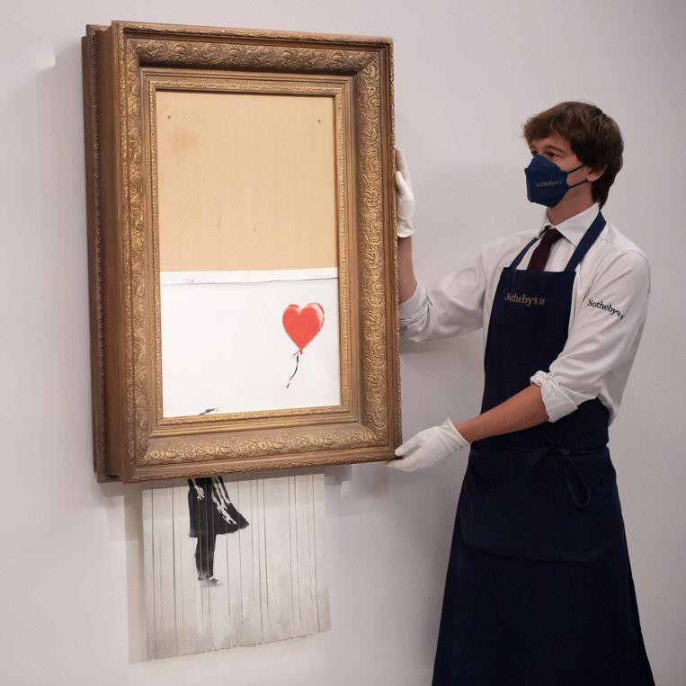 Banksy's 'Love is in the Bin' nadat het zichzelf vernietigd had via een ingebouwde versnipperaar. Beeld Photo News