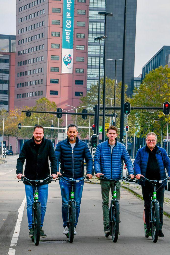 De e-step in actie: als test staan er de komende maanden twintig bij rooftopbar Doloris in Tilburg. Van links naar rechts: horecaondernemer en initiatiefnemer Jaap van Ham, Ben Smit (citymarketing), Teun Verschuren (Citysteps) en Marc Meeuwis (citymarketing).