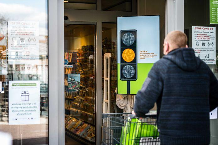 VELDHOVEN - Een stoplicht bij de ingang van een PLUS-filiaal geeft aan hoe druk het is in de winkel.