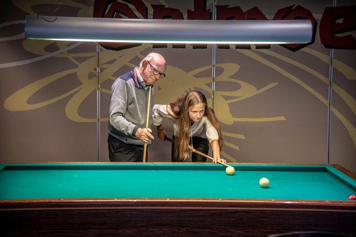 Wim Coenders en kleindochter Laura biljarten in het Overasseltse verenigingsgebouw.