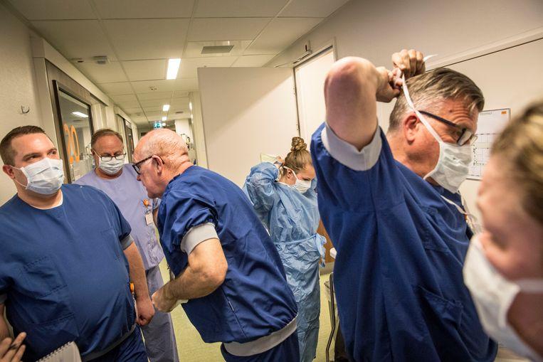 Maasstadziekenhuis Rotterdam, 8 april 2020. Een groep artsen en verpleegkundigen bereidt zich voor om de COVID19-afdeling op te gaan. De foto werd geplaatst bij een verhaal over de schaarste aan beschermingsmateriaal voor zorgpersoneel. 'Ik mocht foto's maken op de ic, wat bijzonder was, die deur houden bijna alle ziekenhuizen dicht. Ik stond in de hoek met ook zo'n pak aan, vrij dichtbij want die ruimtes daar zijn niet groot. Je ziet de concentratie op hun gezicht.' Beeld Arie Kievit