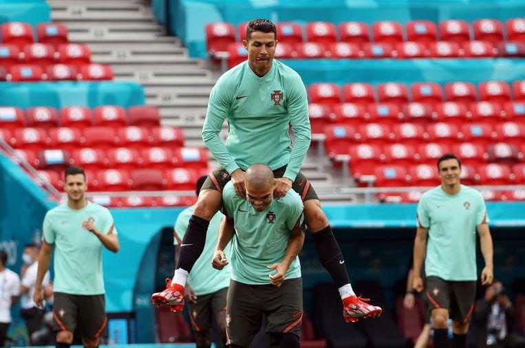 De laatste training van Portugal voor het duel met Hongarije: Cristiano Ronaldo klimt op de rug van Pepe.  Beeld Reuters