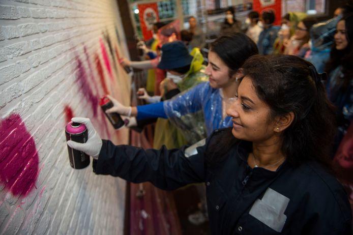 De leerlingen van Stella Maris krijgen een graffitiworkshop. Ook schepen van onderwijs Jinnih Beels steekt de handen uit de mouwen.
