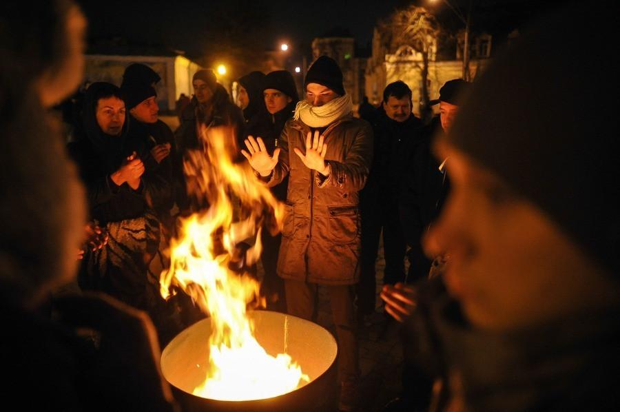 Manifestanten warmen zich op het Mikhaylivskaplein in Kiev.