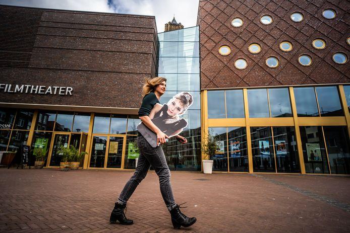 Suzanne Bos van Focus Filmtheater Arnhem met een bordkartonnen Audrey Hepburn op het naar de actrice vernoemde plein in het hart van Arnhem.