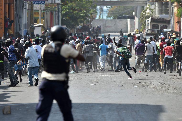 Demonstranten vluchten weg terwijl de Haïtiaanse politie het vuur opent. Beeld AFP