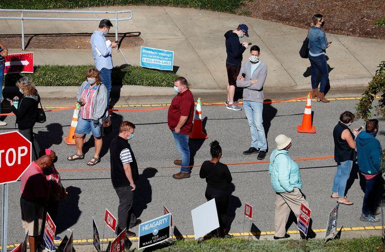 Amerikanen staan in de rij in Cary, North Carolina om vervroegd hun stem uit te brengen.  Beeld AP