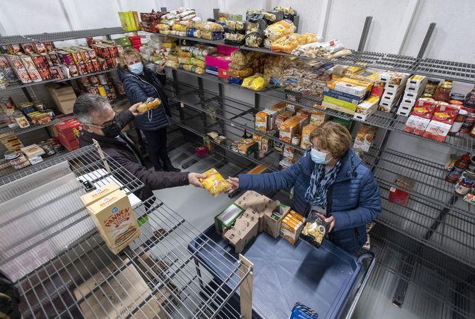 """Vrijwilligers van de pakketcommissie van de Voedselbank Losser bezig met het vullen van de kratten. Links voorzitter Jos in 't Veld. """"We vragen ons af hoe we sommige mensen 'onder de radar', toch over de drempel kunnen krijgen.' Midden Femi Veldhuis en rechts Corrie Knol."""