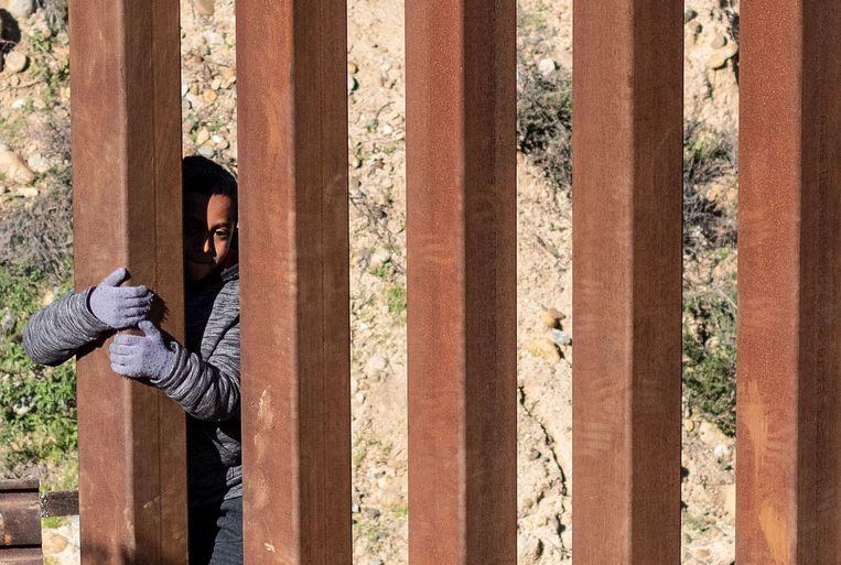 Een Mexicaans jongetje bij het hek dat de VS en Mexico van elkaar scheidt. Beeld AFP