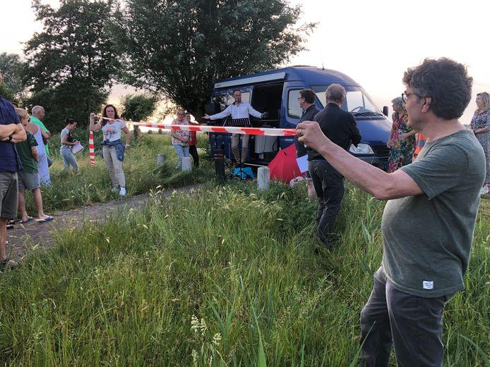 Een rood-wit lint geeft aan tot waar de uitbreiding van de Frankenbeemdweg tot nieuwe rondweg zou moeten komen. Rechts de Osse SP-voorzitter Henk van Gerven.