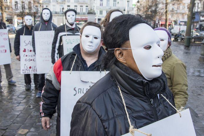 Enkele demonstranten protesteren met maskers op.