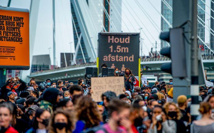 Ondanks herhaalde oproepen stonden betogers op de Erasmusbrug te dicht op elkaar. Waar kruisjes stonden, lukte het betogers wel afstand te houden.