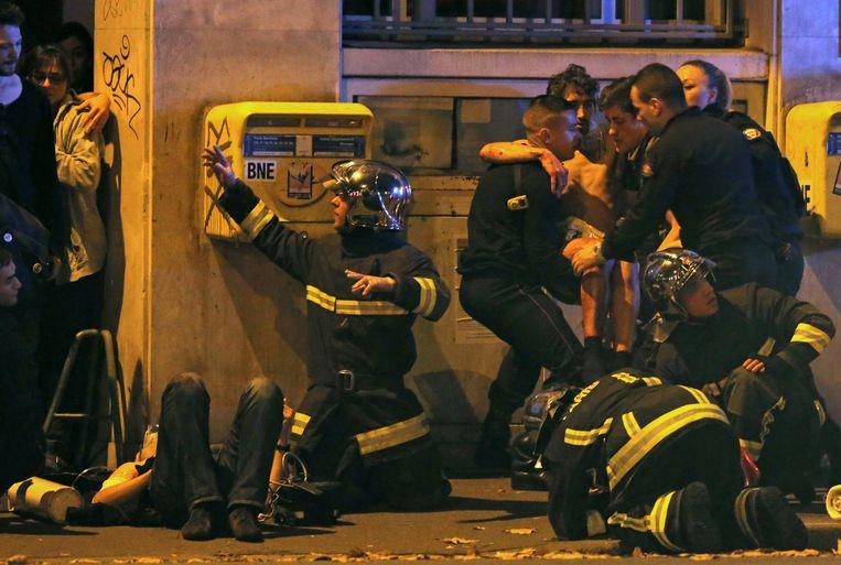 Buiten aan de concertzaal vangen Franse brandweermannen de gewonden op. Azdyne Amimour: 'Mijn zoon was rustig, aardig en behulpzaam. Een engel. Tot hij ineens over de rand kieperde en radicaliseerde. Vanaf dat moment ging alles in een duizelingwekkend tempo.' Beeld REUTERS