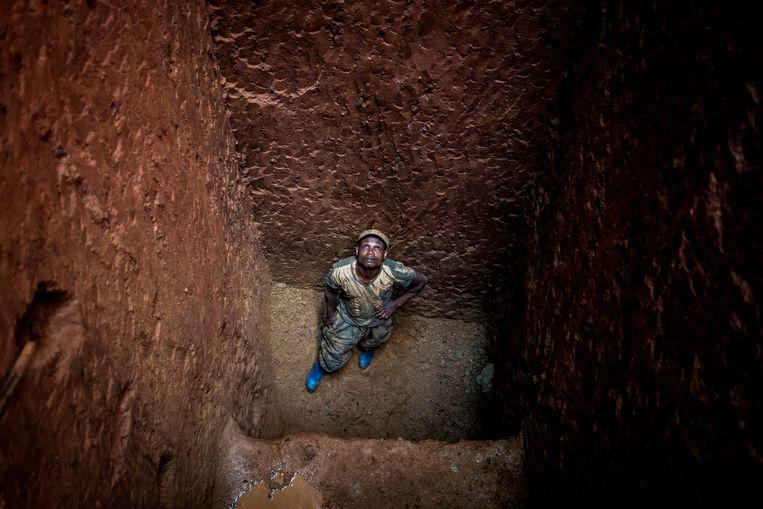 Een mijnwerker in Congo staat op de bodem van een diepe goudmijn in de provincie Ituri.  Beeld AFP