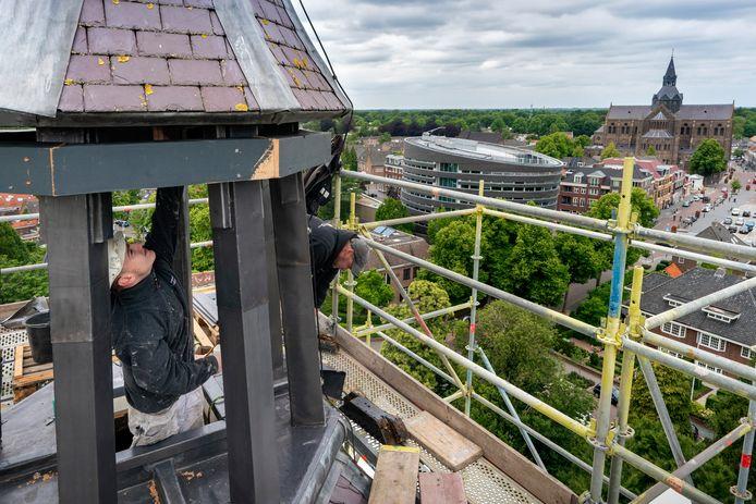 Rico van Gelder (l) van Schildersbedrijf Brabander en Hans Verstegen van leidekkers-loodgietersbedrijf Bogaerts aan het werk op de hoogste toren van het Vughtse raadhuis.