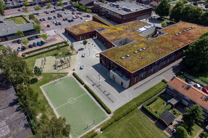 Het Educatief Centrum in Biddinghuizen, met links het veldje en de speeltuin waar hangjongeren overlast veroorzaken.