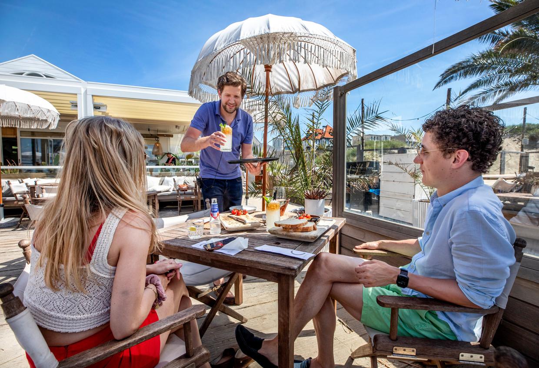 Ramon Hermans (m), eigenaar van Beachclub C, moet wegens personeelsgebrek een handje helpen in de bediening. Beeld Foto Raymond Rutting / de Volkskrant