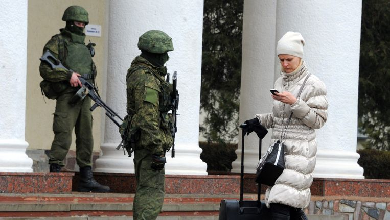 Deze vrouw lijkt zich weinig aan te trekken van de gewapende mannen die de wacht houden voor het vliegveld in Simferopol. Beeld afp
