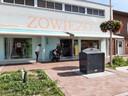 Damesmodezaak Zowiezo, bij de Westermarkt, met voor de deur de gehekelde afvalcontainer.